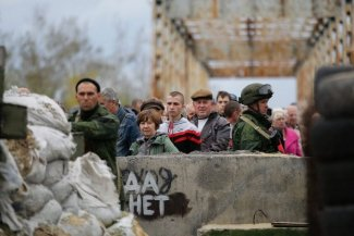 In the picture local ukrainian people and two soldiers on military post on the bridge