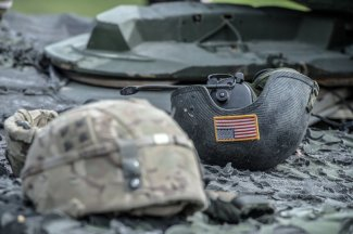 Two soldier helmets, infantry helmet in the foreground, tanker helmet inverted by 180 with the US flag visible in the second.