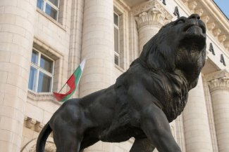 In the foreground is a monument of lion, and in a background is a flag of Bulgaria